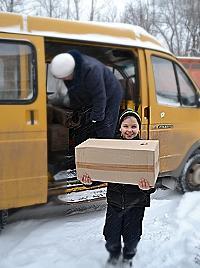 Die Kinder treffen mit Freude das Stiftungsauto und helfen Lebensmitteln ausladen